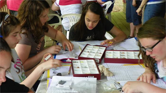The campers do tests on the minerals to determine its characteristics and help them identify it.