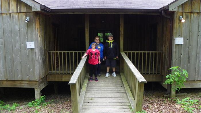 Mrs. Scott with James and Rebekah in front of their cabin.