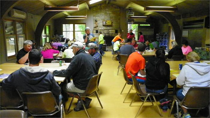 The staff eats lunch while attending the camp staff meeting.
