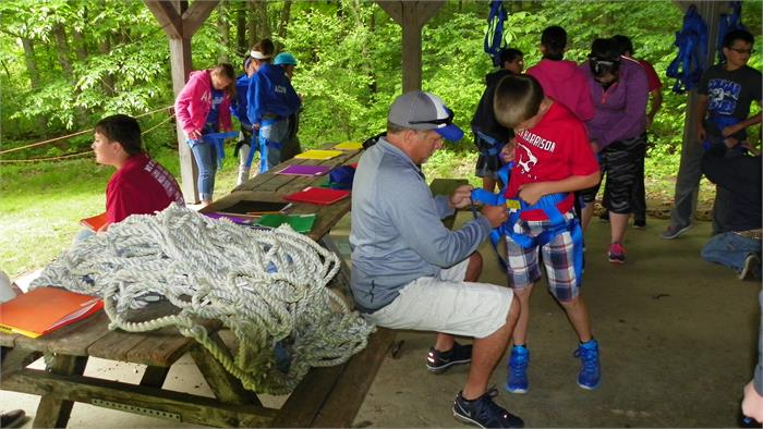 The Climbing Wall - All 40 Feet - Mr. Walker helps a camper tighten the harness.