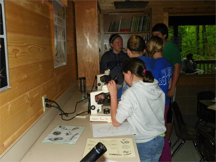 Microscopes: Brandon helps the campers with a question.
